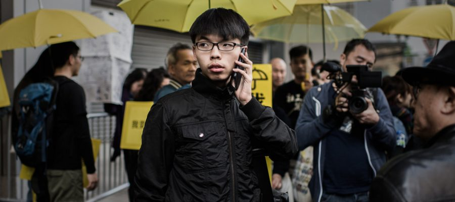 Student activist Joshua Wong talks on the phone after walking out of the Wanchai police station in Hong Kong on January 16, 2015. Student leaders including the teenage face of the pro-democracy movement, Joshua Wong, were charged by police on January 16 as Hong Kong authorities target prominent figures who spearheaded mass rallies.  AFP PHOTO / Philippe Lopez        (Photo credit should read PHILIPPE LOPEZ/AFP/Getty Images)
